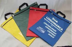 Nos materiais Nylon 70, Bagum, Nylon 600, PVC ou Lona. Medida padrão 34x42cm. Confeccionamos também na medida que atende a sua necessidade. Personalizamos frente e verso sem custo adiciona. Acabamento em gorgurão, alça, fundo simples ou sanfonado e il